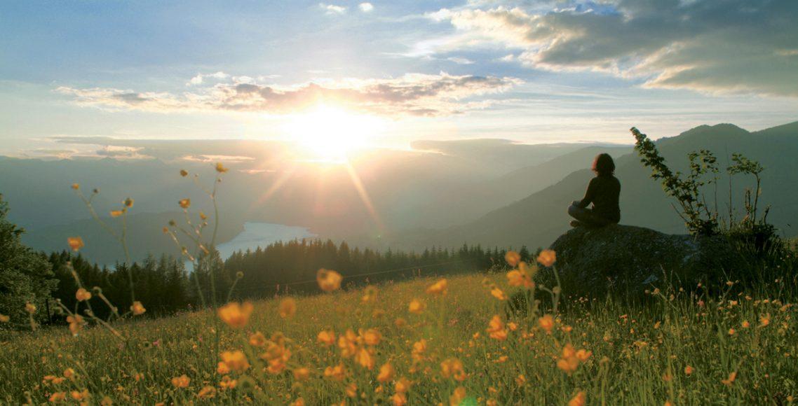 Mensch sitzt auf Stein und blickt in den Sonnenuntergang